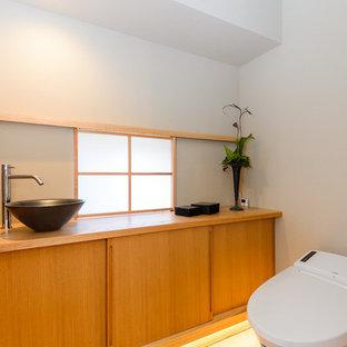 Ejemplo de aseo de estilo zen con armarios con paneles lisos, puertas de armario de madera oscura, paredes blancas, lavabo sobreencimera, encimera de madera y encimeras marrones