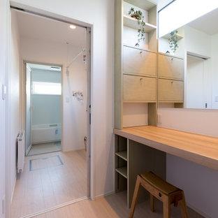 Cette image montre un WC et toilettes chalet de taille moyenne avec un placard à porte plane, des portes de placards vertess, un mur blanc, un sol en bois clair, un lavabo encastré et un plan de toilette en bois.