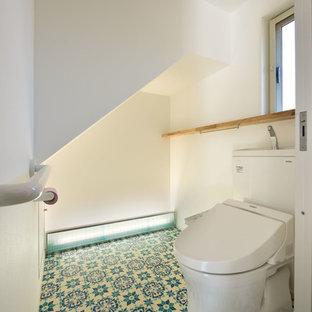 他の地域の小さい北欧スタイルのおしゃれなトイレ・洗面所 (オープンシェルフ、ベージュのキャビネット、一体型トイレ、ラミネートの床、青い床) の写真