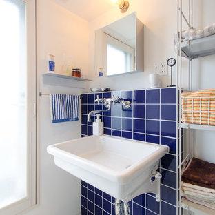 Aménagement d'un petit WC et toilettes industriel avec un placard sans porte, des portes de placard blanches, un carrelage bleu, un carrelage en pâte de verre, un mur blanc et un lavabo suspendu.
