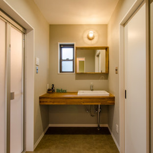 Aménagement d'un petit WC et toilettes industriel avec un mur beige, un sol en vinyl, un lavabo posé, un plan de toilette en bois, un sol marron, un plan de toilette marron, des portes de placard en bois brun, meuble-lavabo encastré, un plafond en papier peint et du papier peint.