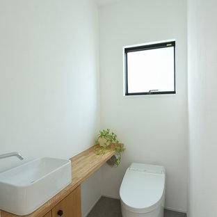 他の地域の中くらいのコンテンポラリースタイルのおしゃれなトイレ・洗面所 (家具調キャビネット、白いタイル、白い壁、グレーの床) の写真