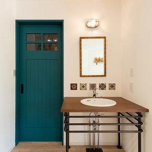 Ispirazione per un piccolo bagno di servizio moderno con pareti bianche, parquet chiaro, lavabo da incasso, top in legno, pavimento beige e top marrone