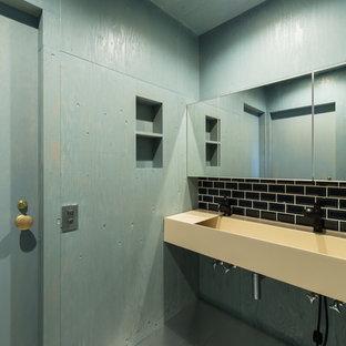 他の地域のコンテンポラリースタイルのおしゃれなトイレ・洗面所 (黒いタイル、青い壁、壁付け型シンク、青い床) の写真