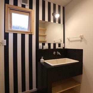他の地域のアジアンスタイルのおしゃれなトイレ・洗面所 (オープンシェルフ、黒いタイル、マルチカラーの壁、無垢フローリング、オーバーカウンターシンク、木製洗面台) の写真