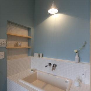 Esempio di un bagno di servizio shabby-chic style con nessun'anta, ante in legno chiaro, piastrelle bianche, piastrelle a mosaico, pareti blu, lavabo da incasso e top piastrellato