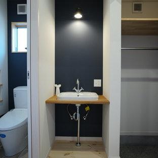 Imagen de aseo asiático con paredes azules, suelo de madera en tonos medios, lavabo bajoencimera y suelo beige
