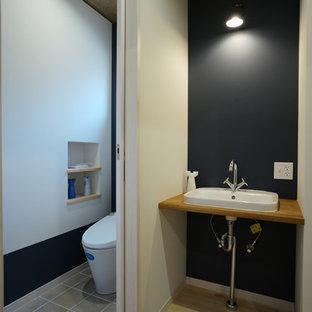 他の地域の北欧スタイルのおしゃれなトイレ・洗面所 (青い壁、無垢フローリング、アンダーカウンター洗面器、ベージュの床、木製洗面台、ブラウンの洗面カウンター) の写真