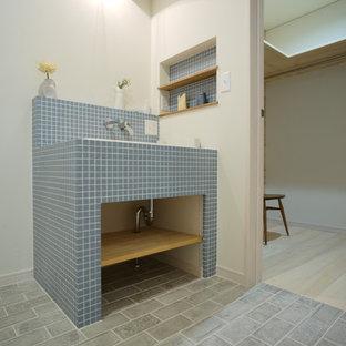Пример оригинального дизайна: туалет в скандинавском стиле с синей плиткой, белыми стенами, столешницей из плитки и серым полом