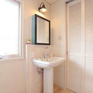 На фото: туалет в скандинавском стиле с фасадами с филенкой типа жалюзи, белыми фасадами, белыми стенами, светлым паркетным полом, раковиной с пьедесталом и столешницей из дерева с