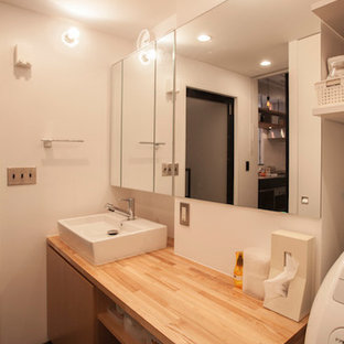 This is an example of a medium sized modern cloakroom in Tokyo with flat-panel cabinets, light wood cabinets, white walls, slate flooring, a vessel sink and wooden worktops.