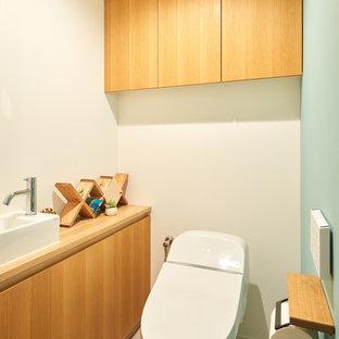 他の地域の北欧スタイルのおしゃれなトイレ・洗面所 (緑の壁、クッションフロア、オーバーカウンターシンク、グレーの床) の写真