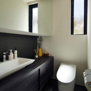 他の地域のコンテンポラリースタイルのおしゃれなトイレ・洗面所 (黒いキャビネット、ビデ、白いタイル、白い壁、磁器タイルの床、オーバーカウンターシンク、木製洗面台、グレーの床、黒い洗面カウンター、造り付け洗面台、壁紙) の写真