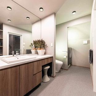 На фото: туалеты среднего размера в стиле модернизм с фасадами островного типа, коричневыми фасадами, унитазом-моноблоком, серыми стенами, полом из ламината, накладной раковиной, столешницей из искусственного камня, серым полом и белой столешницей