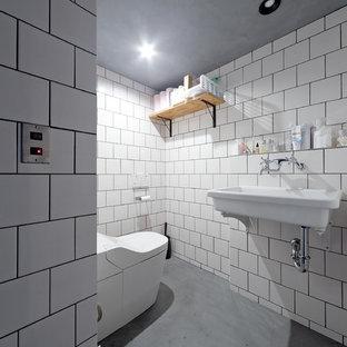 大阪の小さいインダストリアルスタイルのおしゃれなトイレ・洗面所 (白い壁、コンクリートの床、壁付け型シンク、グレーの床) の写真