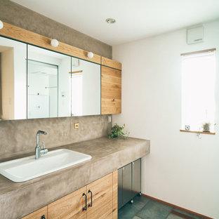 名古屋のラスティックスタイルのおしゃれなトイレ・洗面所 (フラットパネル扉のキャビネット、中間色木目調キャビネット、白い壁、オーバーカウンターシンク、緑の床) の写真