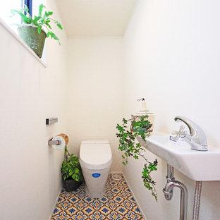 Diseño de aseo asiático con paredes blancas, lavabo tipo consola y suelo multicolor