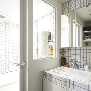 他の地域のインダストリアルスタイルのおしゃれなトイレ・洗面所 (インセット扉のキャビネット、白いキャビネット、白いタイル、磁器タイル、白い壁、タイルの洗面台、白い洗面カウンター) の写真