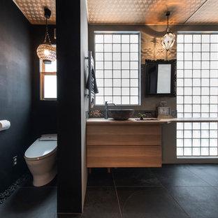 東京23区のコンテンポラリースタイルのおしゃれなトイレ・洗面所 (フラットパネル扉のキャビネット、中間色木目調キャビネット、黒い壁、ベッセル式洗面器、木製洗面台、黒い床、ブラウンの洗面カウンター) の写真