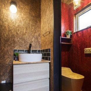 Пример оригинального дизайна: туалет в стиле лофт с плоскими фасадами, светлыми деревянными фасадами, черной плиткой, коричневыми стенами, паркетным полом среднего тона, настольной раковиной и коричневым полом