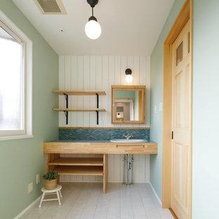Nordische Gästetoilette mit offenen Schränken, blauer Wandfarbe, gebeiztem Holzboden, Einbauwaschbecken und weißem Boden in Sonstige