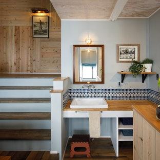 他の地域の北欧スタイルのおしゃれなトイレ・洗面所 (オープンシェルフ、白いキャビネット、マルチカラーのタイル、グレーの壁、無垢フローリング、オーバーカウンターシンク、木製洗面台、茶色い床) の写真
