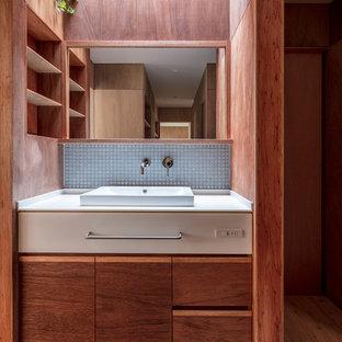 Idee per un bagno di servizio nordico con ante lisce, ante marroni, piastrelle grigie, piastrelle a mosaico, pareti marroni, parquet scuro, lavabo a bacinella, top in superficie solida e pavimento beige