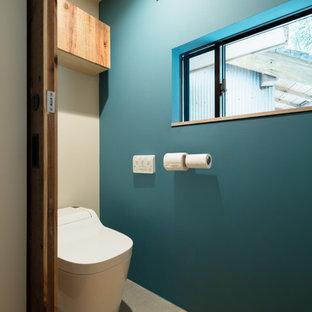 Imagen de aseo asiático, pequeño, con sanitario de una pieza, paredes azules y suelo de madera en tonos medios