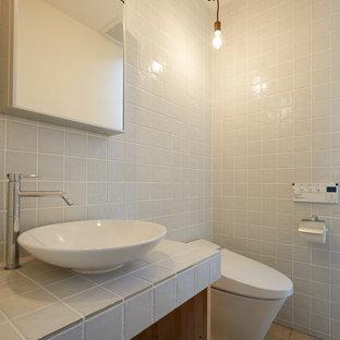 他の地域の小さいエクレクティックスタイルのおしゃれなトイレ・洗面所 (白いタイル、テラコッタタイルの床、ベッセル式洗面器、タイルの洗面台、茶色い床、白い洗面カウンター、オープンシェルフ、白いキャビネット、ビデ、磁器タイル、白い壁) の写真