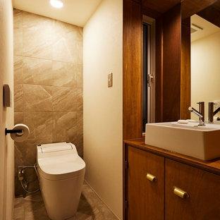 他の地域の中くらいのモダンスタイルのおしゃれなトイレ・洗面所 (フラットパネル扉のキャビネット、濃色木目調キャビネット、ビデ、グレーのタイル、磁器タイル、茶色い壁、磁器タイルの床、ベッセル式洗面器、木製洗面台、グレーの床、ブラウンの洗面カウンター) の写真