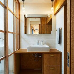 他の地域の中くらいのモダンスタイルのおしゃれなトイレ・洗面所 (フラットパネル扉のキャビネット、濃色木目調キャビネット、白いタイル、磁器タイル、白い壁、磁器タイルの床、ベッセル式洗面器、木製洗面台、グレーの床、ブラウンの洗面カウンター) の写真