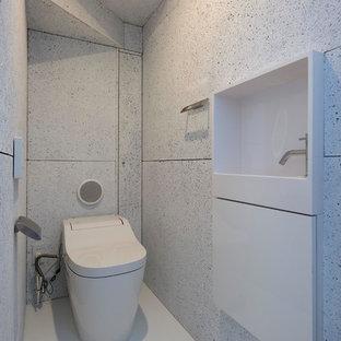 他の地域のコンテンポラリースタイルのおしゃれなトイレ・洗面所 (フラットパネル扉のキャビネット、白いキャビネット、白い壁、白い床) の写真