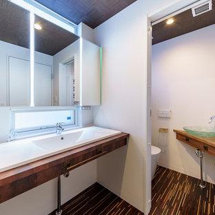 Diseño de aseo asiático con armarios abiertos, sanitario de una pieza, baldosas y/o azulejos blancos, paredes blancas, suelo de madera oscura, lavabo encastrado, encimera de laminado y suelo negro