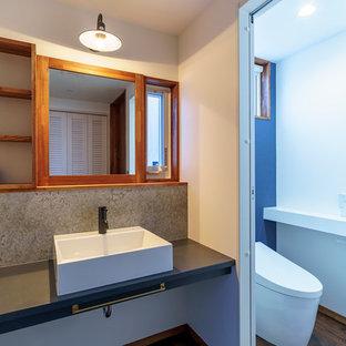 На фото: туалет в стиле лофт с открытыми фасадами, фасадами цвета дерева среднего тона, унитазом-моноблоком, черно-белой плиткой, цементной плиткой, белыми стенами, темным паркетным полом, настольной раковиной, столешницей из ламината и коричневым полом с