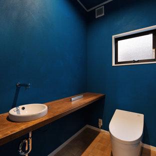 Cette image montre un WC et toilettes bohème avec un mur bleu, un sol en carreau de terre cuite, un lavabo posé, un plan de toilette en bois, un sol bleu et un plan de toilette marron.