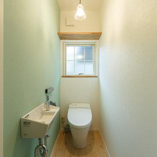 Идея дизайна: туалет в современном стиле с унитазом-моноблоком, разноцветными стенами, светлым паркетным полом, подвесной раковиной и бежевым полом