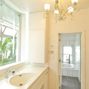 他の地域のヴィクトリアン調のおしゃれなトイレ・洗面所 (レイズドパネル扉のキャビネット、白いキャビネット、白い壁、一体型シンク、ベージュの床) の写真