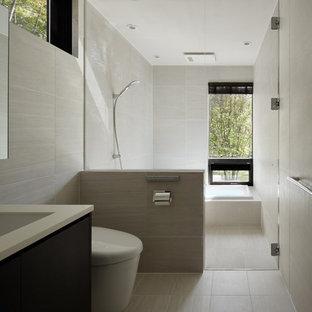 他の地域のコンテンポラリースタイルのおしゃれなトイレ・洗面所 (フラットパネル扉のキャビネット、濃色木目調キャビネット、グレーの壁、一体型シンク、グレーの床) の写真