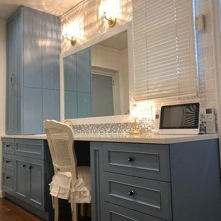 Idee per un bagno di servizio tradizionale con consolle stile comò, ante blu, WC monopezzo, piastrelle multicolore, piastrelle a mosaico, pareti bianche, pavimento in legno massello medio, lavabo integrato, top in superficie solida, pavimento marrone e top bianco