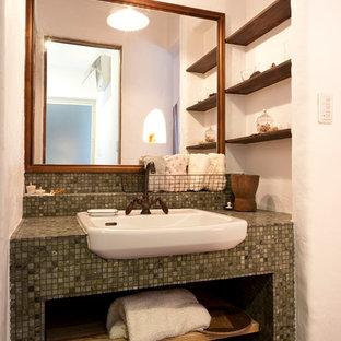 福岡の小さい地中海スタイルのおしゃれなトイレ・洗面所 (青いタイル、磁器タイル、タイルの洗面台、青い洗面カウンター、白い壁、無垢フローリング、オーバーカウンターシンク、茶色い床) の写真