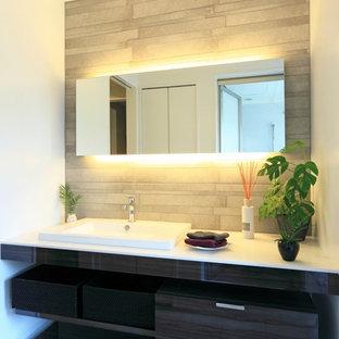 Пример оригинального дизайна: туалет в современном стиле с плоскими фасадами, черными фасадами, белыми стенами, накладной раковиной и серым полом
