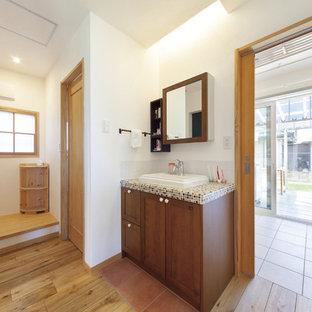 На фото: туалеты в стиле модернизм с фасадами с декоративным кантом, темными деревянными фасадами, коричневой плиткой, белыми стенами, паркетным полом среднего тона, настольной раковиной, столешницей из плитки, коричневым полом и коричневой столешницей
