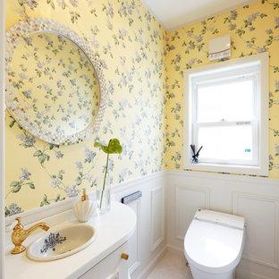 他の地域のトラディショナルスタイルのおしゃれなトイレ・洗面所 (落し込みパネル扉のキャビネット、白いキャビネット、黄色い壁、ベージュの床) の写真