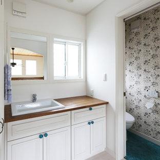 他の地域の北欧スタイルのおしゃれなトイレ・洗面所 (落し込みパネル扉のキャビネット、白いキャビネット、白い壁、オーバーカウンターシンク、木製洗面台、マルチカラーの床) の写真