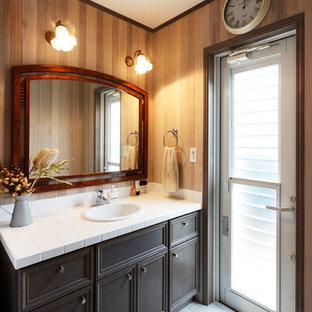 На фото: туалет в стиле ретро с фасадами с утопленной филенкой, черными фасадами, коричневыми стенами, накладной раковиной и столешницей из плитки с