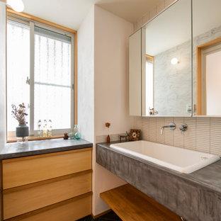 Esempio di un bagno di servizio etnico di medie dimensioni con piastrelle bianche, piastrelle a listelli, pavimento con piastrelle in ceramica, nessun'anta, pareti bianche, lavabo da incasso, top in cemento, pavimento nero e top grigio
