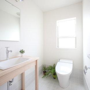 На фото: туалет среднего размера в скандинавском стиле с белыми стенами, светлым паркетным полом и бежевым полом с