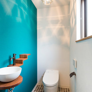 他の地域のコンテンポラリースタイルのおしゃれなトイレ・洗面所 (青い壁、一体型トイレ、モザイクタイル、ベッセル式洗面器、マルチカラーの床) の写真