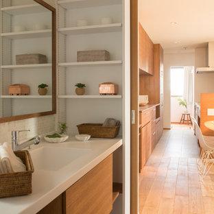 На фото: туалет в скандинавском стиле с плоскими фасадами, коричневыми фасадами, белыми стенами, паркетным полом среднего тона, монолитной раковиной и коричневым полом