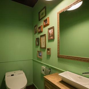 Idée de décoration pour un WC et toilettes tradition de taille moyenne avec un mur vert, une vasque, un plan de toilette en bois, un placard avec porte à panneau encastré, des portes de placard en bois clair, un plan de toilette marron, un WC à poser, sol en stratifié et un sol marron.